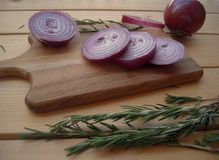 Red onion chopped on a cuttering board and rosemary sprigs. Red onion chopped on a cuttering board and rosemary sprigs, rustic style, fragrant seasoning Royalty Free Stock Photos