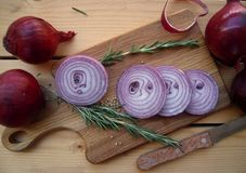 Red onion chopped on a cuttering board, sprigs of rosemary and coriander seeds. Red onion chopped and sprigs of rosemary on a rustic table, prepared for cooking Royalty Free Stock Photo