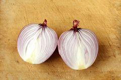 Red onion cut in half on wood Royalty Free Stock Image