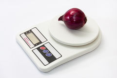 Red onion on a digital white kitchen scale Stock Images