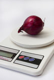 Red onion on a digital white kitchen scale Royalty Free Stock Images