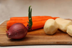 Red onion with feather, peeled potatoes and carrots on the chopping board. Royalty Free Stock Images