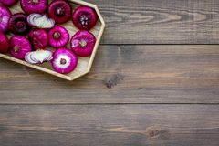 Red onion is healthy product. Onion bulbs in tray on dark wooden background top view copy space. Red onion is healthy product. Onion bulbs in tray on dark wooden Stock Image