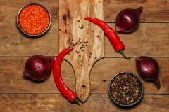 Red onion, pepper, egg, spices on a wooden table. View from above. Spices with vegetables and eggs on an old wooden table. Still l stock photo