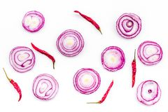 Red onion rings as seasoning. Onion near chili peper, garlic on white background top view pattern. Red onion rings as seasoning. Onion near chili peper, garlic Stock Photos