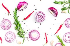 Red onion rings as seasoning. Onion near chili peper, rosemary, black peper, garlic on white background top view.  Royalty Free Stock Photo