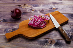 Red onion. Rings of red onion and knife Stock Photos