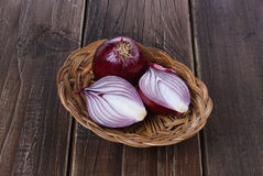 Red onion on a rustic wooden background. Group of red (purple) onions in a straw basket on a rustic wooden background stock photos