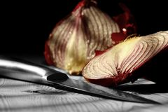 Red onion sliced on wood with a knife Stock Image