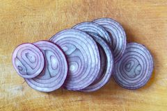 Red onion slices. On kitchen board Stock Photos