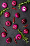 Red onion among spices rosemary, chili peper on black background top view.  Stock Photos
