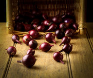 Red onion vegetables with wicker basket in background on rustic Stock Images