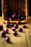Red onion vegetables with wicker basket in background on rustic Stock Image