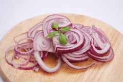 Red onions. Some fresh red onions on a wooden plate Royalty Free Stock Photography