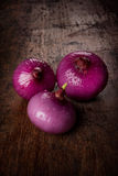 Red onions. A fresh red onions on wood table Royalty Free Stock Image