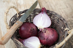 Red onions in a basket with knife. Some red onions in a basket with knife Stock Photo
