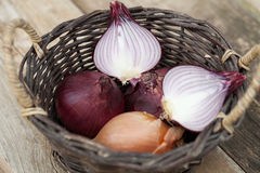 Red onions in a basket with knife. Some red onions in a basket with knife Stock Images