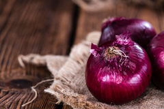 Red Onions (close-up shot). Some fresh Red Onions (close-up shot) on an wooden table Royalty Free Stock Photography