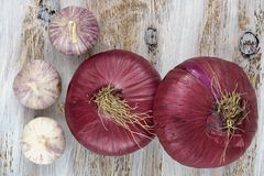 Red onions and garlic on the white painted wooden background. Stock Photos