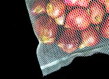 Red onions in mesh bag and some on floor  on black backg. Round Stock Images