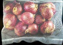 Red onions in mesh bag and some on floor isolated on black backg. Round stock images