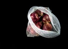 Red onions in mesh bag and some on floor isolated on black backg. Round stock photos