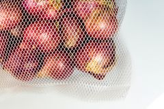 Red onions in mesh bag and some on floor isolated on white backg. Round Royalty Free Stock Images