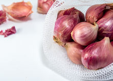 Red onions in mesh bag   on white background. Red onions in mesh bag and some on floor  on white background Stock Photo