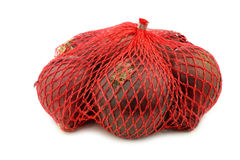 Red onions in a red plastic net Royalty Free Stock Photography