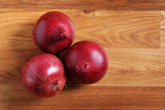 Red onions. Shot from above on wooden table stock image