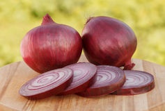 Red onions. With slices on chopping board Royalty Free Stock Images
