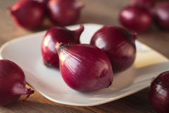Red onions. On white plate and scattered on the table Stock Photos