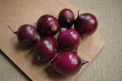 Red onions on a wooden board royalty free stock images