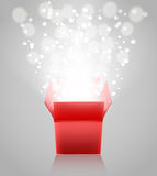 Red open box with light rays on grey background Stock Images