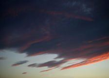 Red orange and blue clouds at sunset Royalty Free Stock Images
