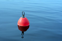 Red-orange buoy in the blue water. Red-orange plastic buoy with iron loop on the blue water royalty free stock photo