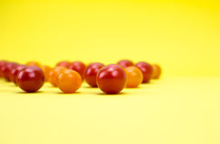 Red and orange cherry tomatoes. On yellow background Stock Photos