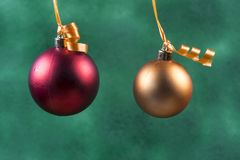 red christmas ball hanging with orange ribbon on green background royalty free stock images