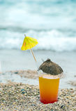 Red and orange cocktail with a straw and umbrella on the beach with waves, Stock Images