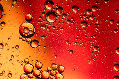 Red and Orange Coloured Oil on Water Abstract Stock Images