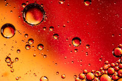Red and Orange Coloured Oil on Water Abstract Stock Photo