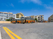 The red and orange coloured retro-styled Maltese public buses. BUGIBBA, MALTA - JUNE 14, 2005: The red and orange coloured retro-styled Maltese public buses stay Royalty Free Stock Photography