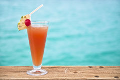 Red - orange drink by turquoise sea. Glass with a cold drink at a beach Stock Images