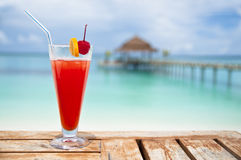 Red - orange drink by turquoise sea. Glass with a cold drink at a beach Stock Photo