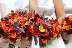 Red and orange flower bouquet. On a wedding dress Royalty Free Stock Photography