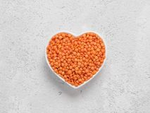 Red orange lentil Football in heart bowl on gray cement background Royalty Free Stock Photos