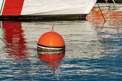 Red and orange mooring buoy in the port. Red and orange buoy for mooring boats on the surface of the water in the port. Mediterranean sea, Italy stock photos