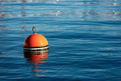 Red and orange mooring buoy in the sea. One red and orange buoy for mooring boats on the surface of the water. Mediterranean sea, Italy royalty free stock photo