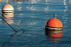 Red and orange mooring buoys in the port. Two red and orange buoy for mooring boats on the surface of the water in the port. Mediterranean sea, Italy stock photo