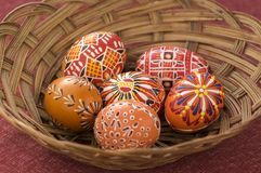 Red and orange painted Easter eggs in brown wicker basket, traditional Easter still life Royalty Free Stock Photo